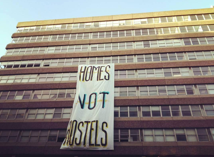 A banner hangs of a building. On it is written Homes not Hostels.