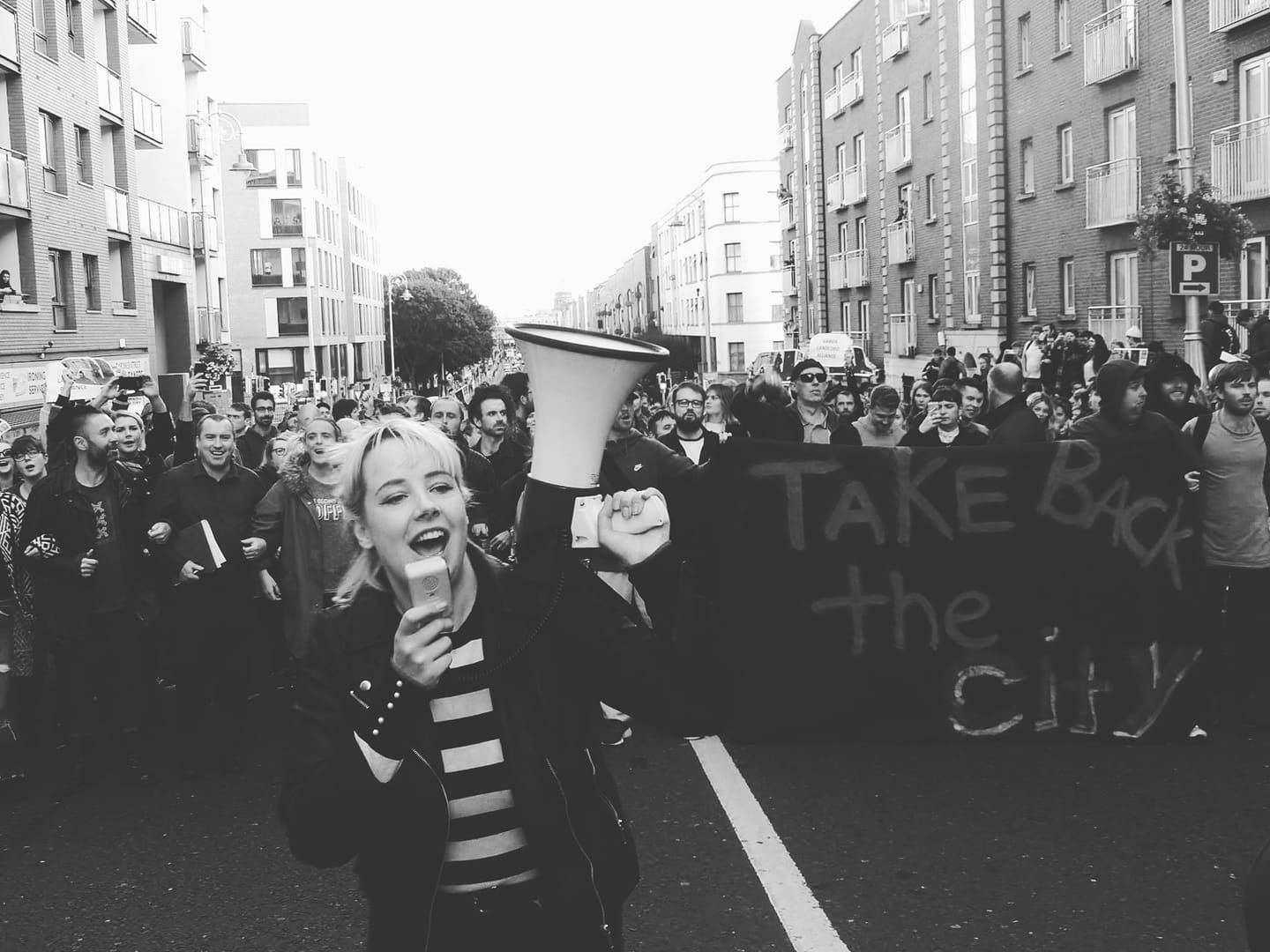 Protesters of the Take Back the City Dublin movement are walking down the street. A girl is holding a megaphone. The activists militate for a right to housing.