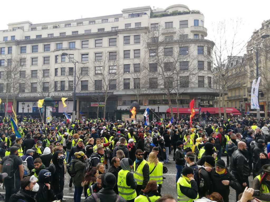 """Protesters of the Gilets-Jaunes movement in France unite at the Champs-Elysees in Paris for the 18th saturday. Many of the persons are wearing yellow vests on the boulevard going from Arc de Triomphe to the river """"Seine"""". Image by Urbanauth"""