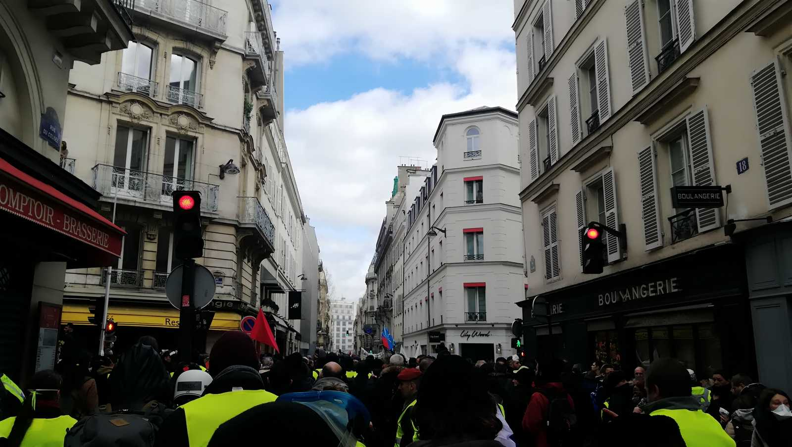Protesters of the Gilets Jaunes movement are walking in a street of Paris.