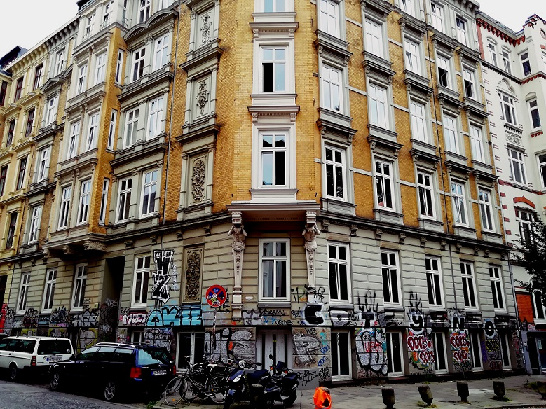 The facade of an building in Berlin made of yellow bricks looks like built around 1920. In front of the building are some cars, bikes and scooters. The walls are full of different Graffiti. Image by Urbanauth.