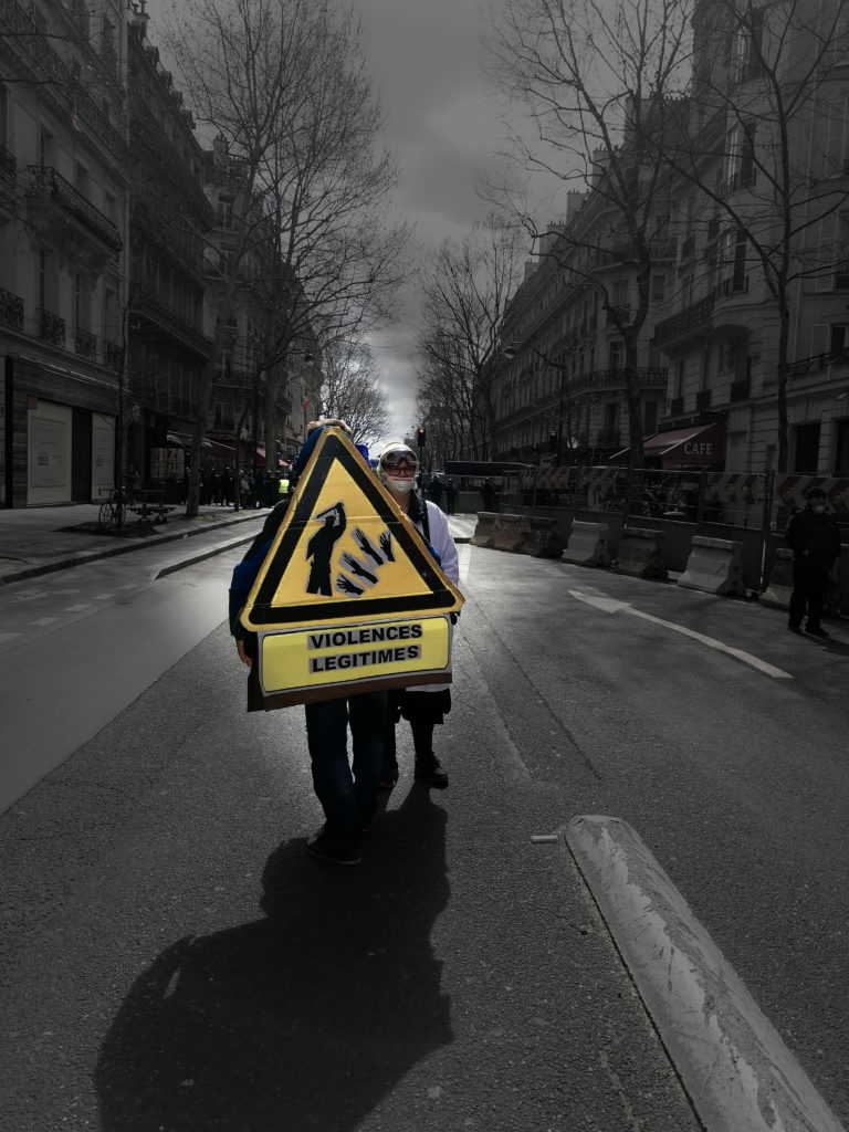 """Two protesters of the Yellow Vest mouvement are standing on a street in Paris near the Champs-Elysee. one of the demonstrators is wearing a costume in the form of a warning sign that says: """"Legit Violence"""", while a dark silhouette can be seen beating on hands on the sign. ."""
