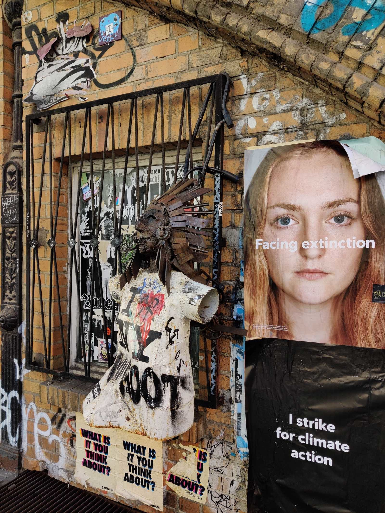 """Pasted upon a Wall in Berlin: """"Facing Extinction - I strike for climate action"""". Beside of the poster, a chaotic artsy wall in the typical flair of Germany's capital."""