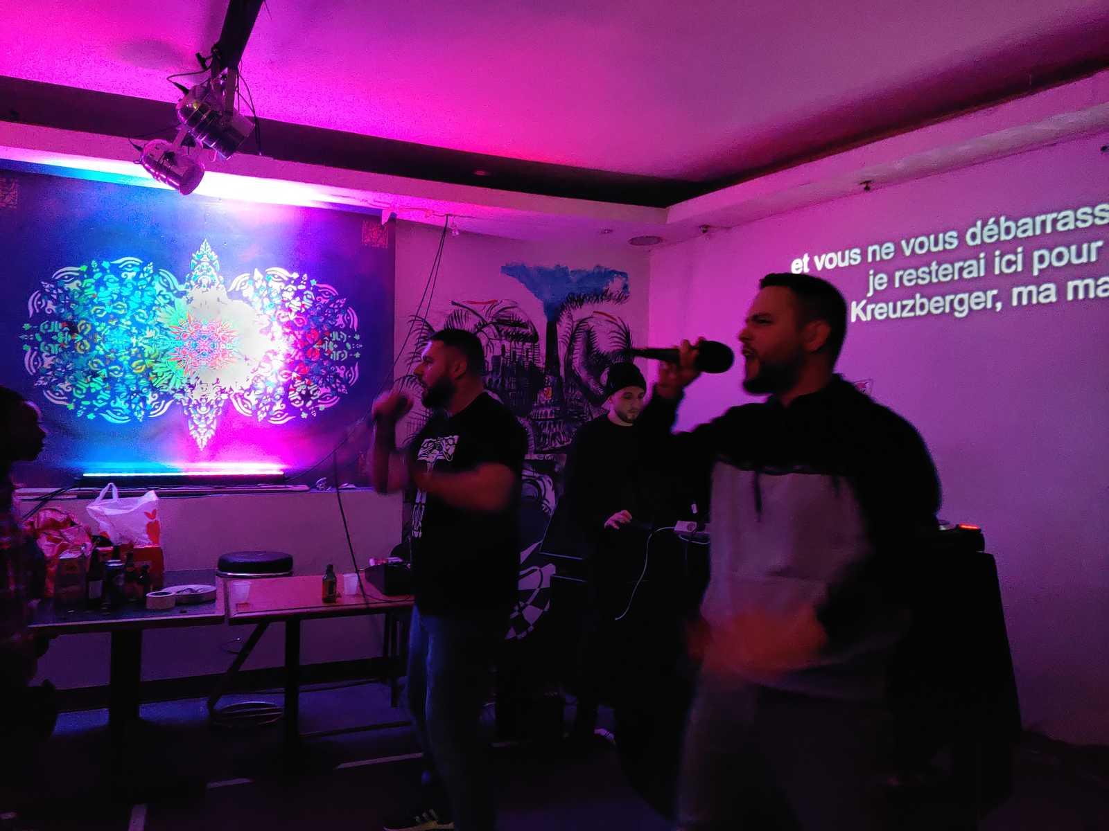 The german Rapper PTK performing in the Aubergine 3000. Behind the translations of his lyrics made by Urbanauth can be percieved, while on the left side a fractalic urban art design by Erwa.One is illuminated in different lights.