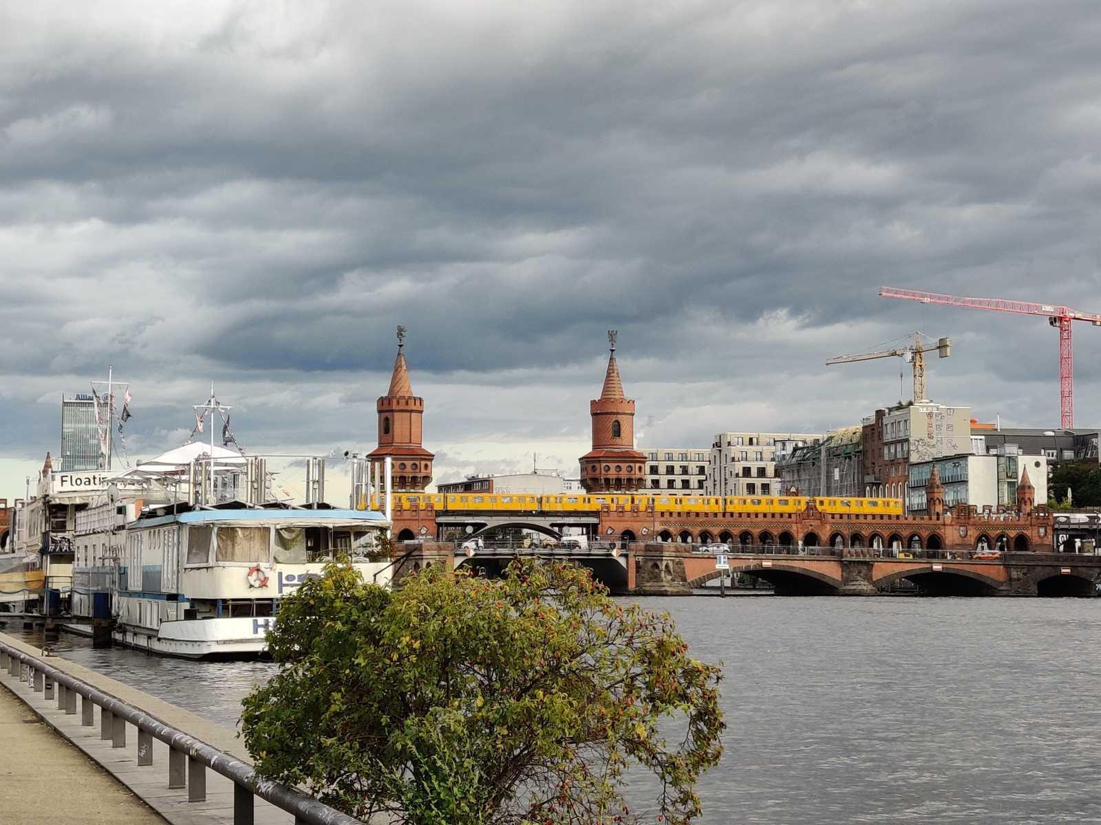 Blick auf die Oberbaumbrücke in Berlin, vom Spree-Ufer aus. Ein weißes Boot, welches eine Touristenunterkunft ist, liegt am Ufer an. Die gelben U-Bahnwägen der BVG ziehen auf der Brücke durch das Bild. Der Himmel ist von grauen Wolken bedeckt.