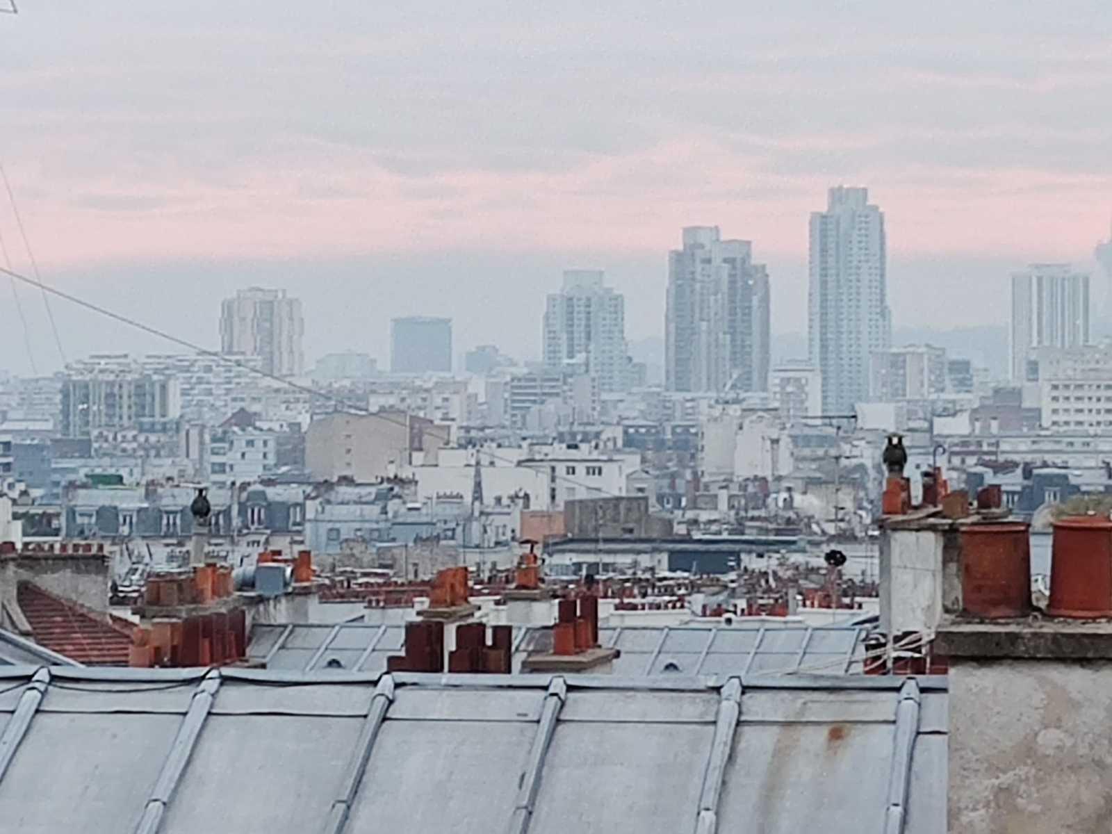 Sicht über Häuserdächer Paris Montmartre Sacre Coeur Miethaie Marchands de sommeils. Smog am Horizont