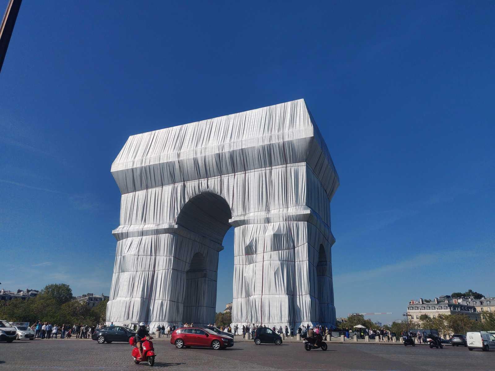 Paris, der verhüllte Triomphbogen vom Arc de Triomphe. Blauer Himmel. Viel Autoverkehr. Verhüllungskunst von Christo und Jeanne-Claude in einem posthumen Projekt. Das Gewebe zum verhüllen scheint silber und hinterlässt Falten.