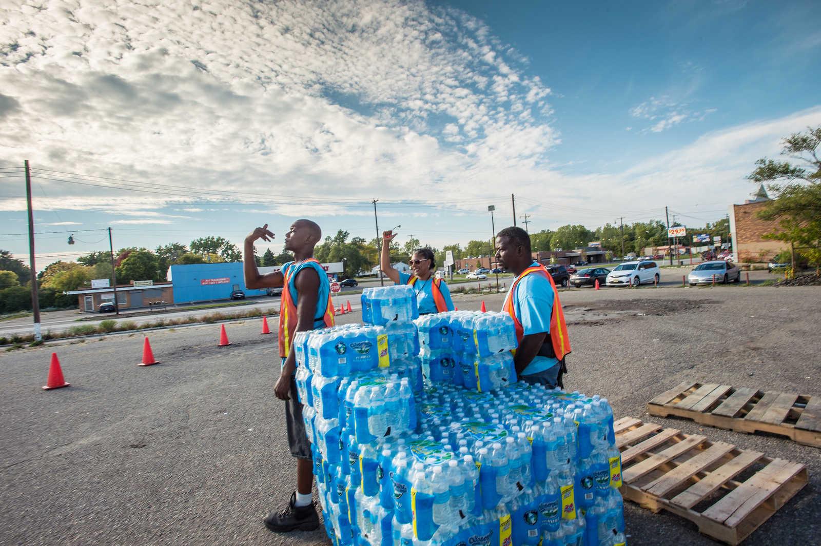 Trinkwasserflaschen auf Paletten mit Helfern in orangenen Jacken auf einem Parkplatz in Flint, Michigan, USA. Flint's Wasserkrise führte dazu, dass das Wasser aus dem Wasserhahn nicht mehr bekömmlich war. Himmel blau leicht bewölkt. Helfer sind people of color.